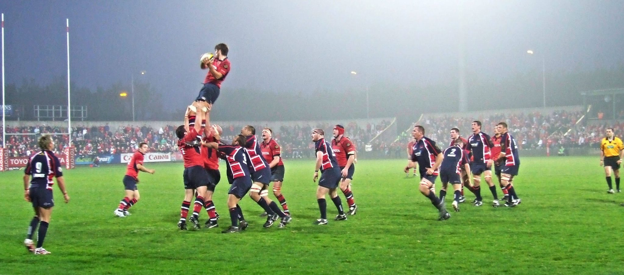 A player in a line out catches the ball during a game of rugby
