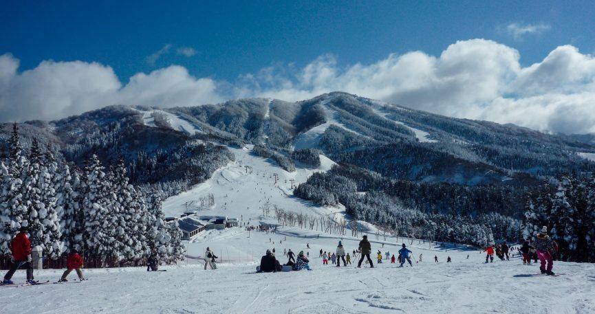 Skiers and snowboarders on the piste at Japan's beautiful Hakuba Valley ski resort