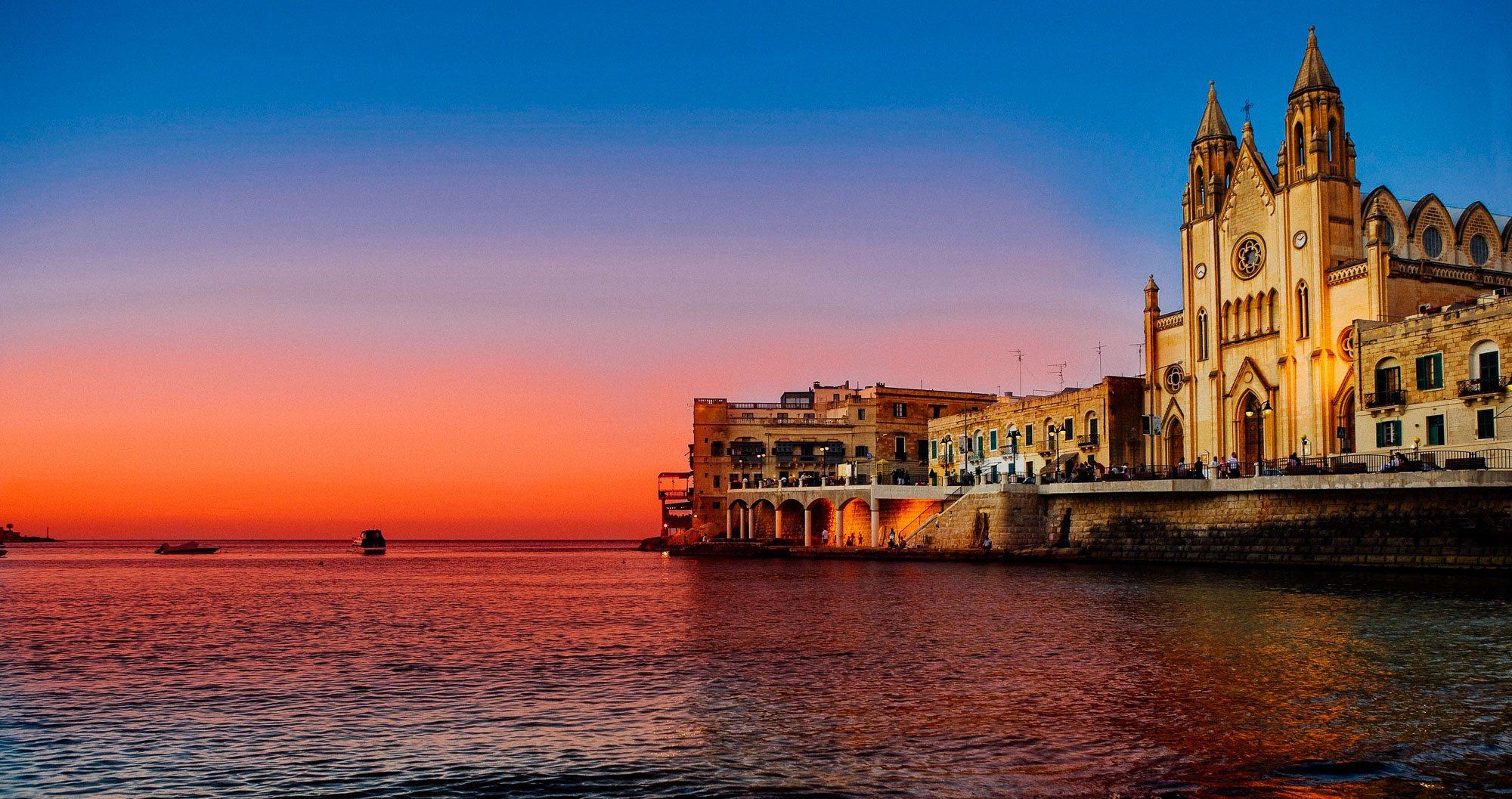 The sun sets over St Julian's Bay in Malta