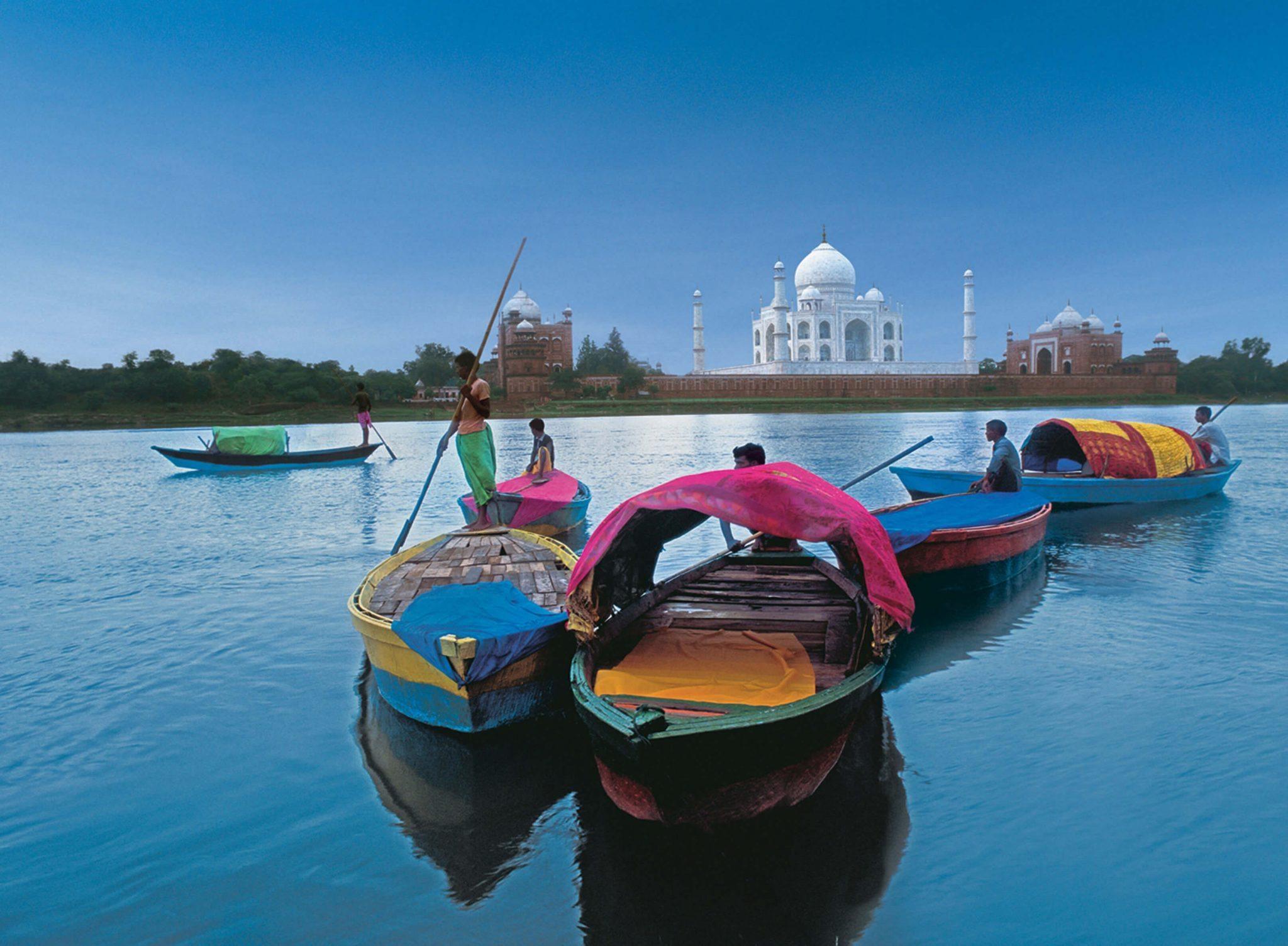 Men in boats cross the river, ahead of the Taj Mahal