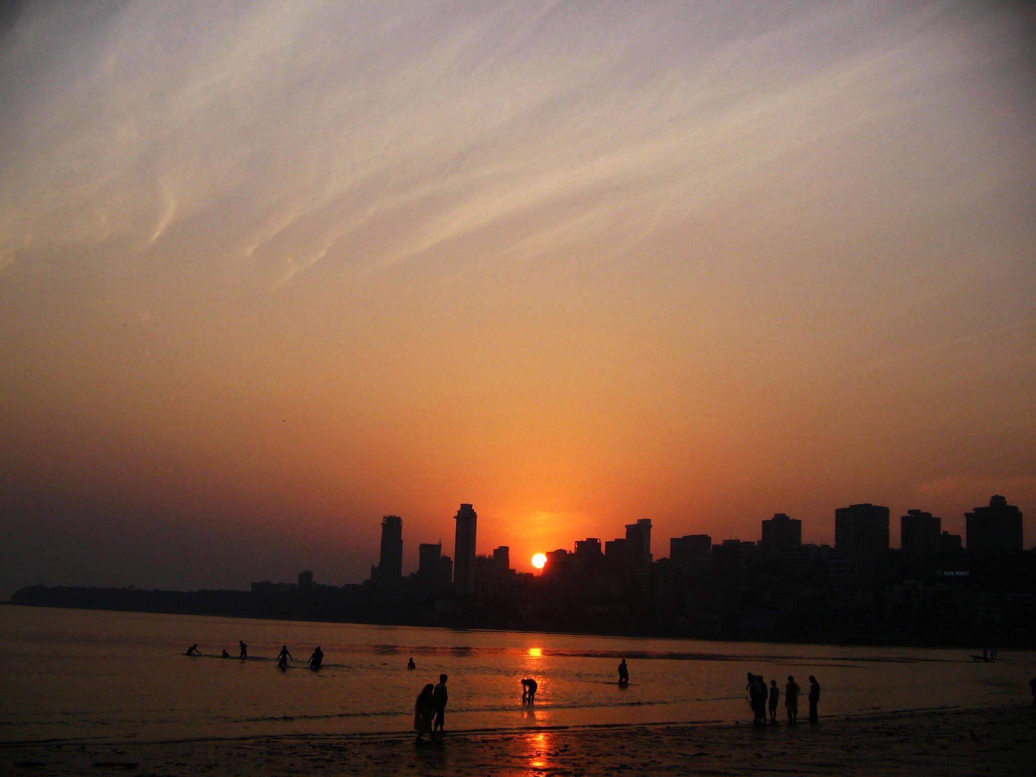 People bathe in the sea as the sun sets on Mumbai beach