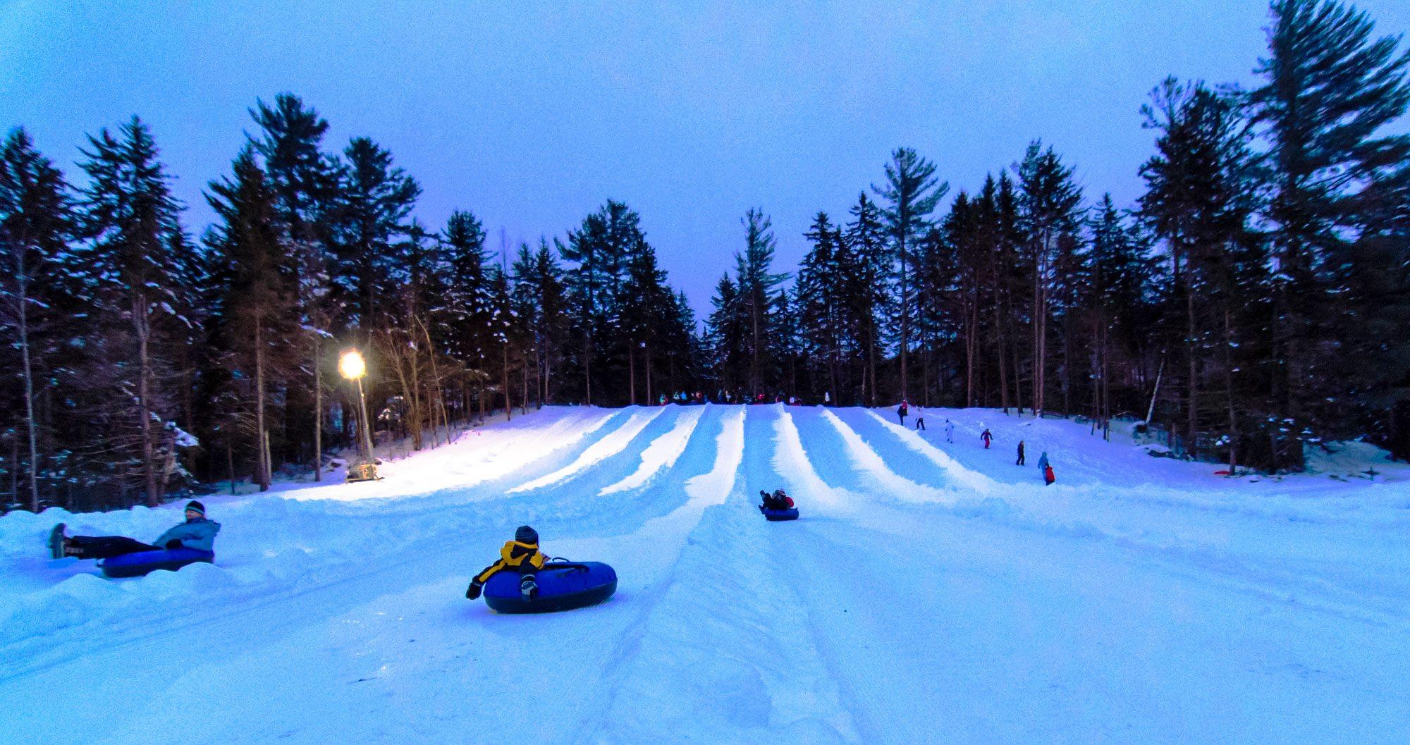 People enjoying tubing at dusk - Waterville ski resort